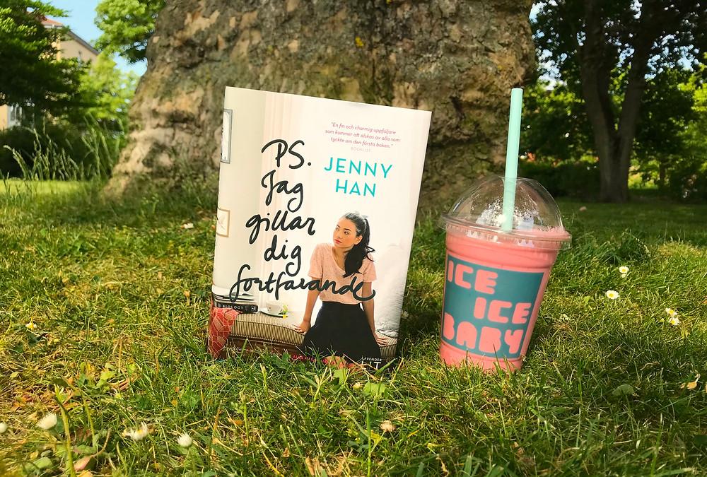 I förgrunden står boken Ps jag gillar dig fortfarande, bredvid står en ta med mugg med rosa smoothie i. I bakgrunden syns en gräsmatta och en trädstam
