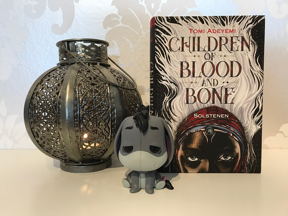 Boken Children of blood and bone står intill en diskret mönstrad tapet i silver och vit. Bredvid boken står en silvrig ljuslykta och framför alltihop står en funko pop figur av I-or