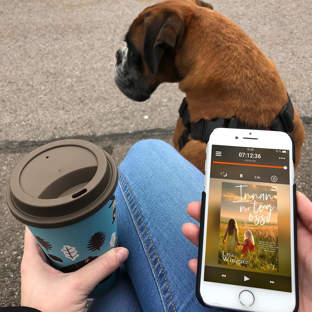 """Benen på en person som sitter på en bänk med en kaffemugg i handen och en vit iPhone med ljudboken: """"Innan ni tog oss"""", synlig på skärmen. Bredvid personen sitter en stor hund."""
