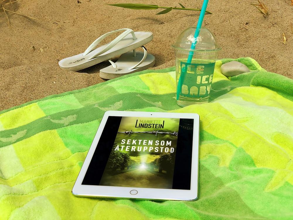 Mitt i bilden syns en vit ipad med omslaget till boken Sekten som återuppstod synlig på skärmen. Ipaden ligger på en grönrandig handduk och i bakgrunden syns en ta med mugg med iste i och ett par vita flipp flopp som ligger i sanden.