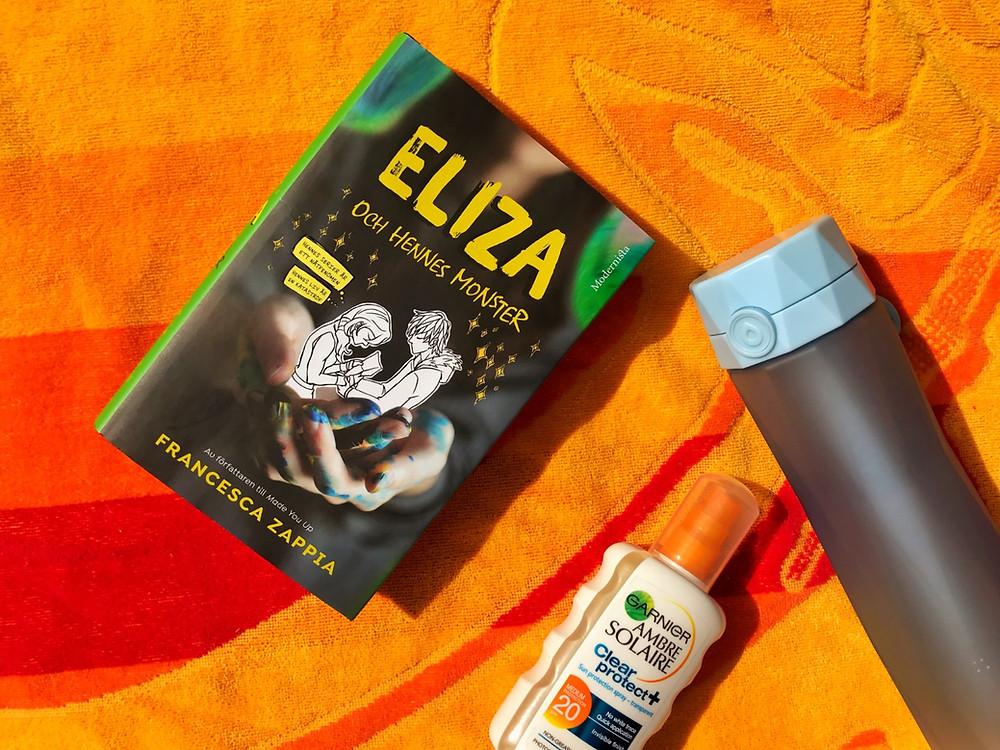 På bilden syns boken Eliza och hennes monster. Boken ligger på en orange strandhandduk med en blå vattenflaska från Hidrate Spark och en solkräm bredvid.