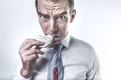 unhealthy eating habits: a photo of a man eating some junk food