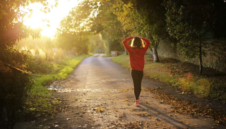 healthy lifestyle habits: a photo of a woman walking down the road