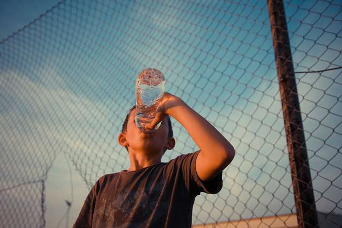 tips to drink more water: a photo of a kid drinking a bottle of water