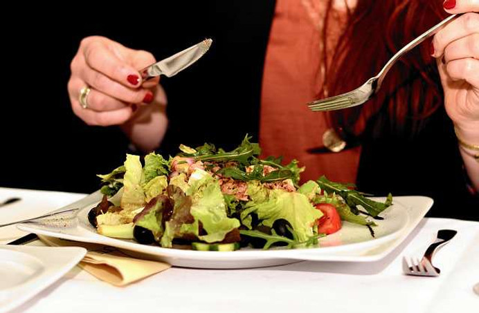 Benefits of healthy food: a photo of a woman eating a healthy salad at a restauran