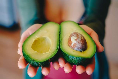 Foods that reduce anxiety and stress: a photo of a woman holding an avocado