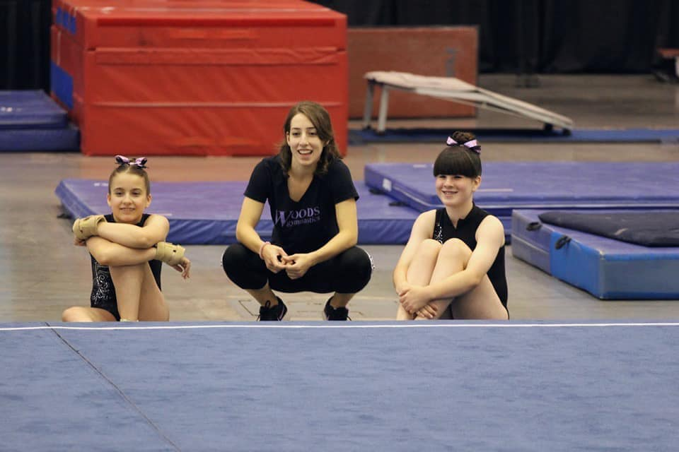 gymnasts and coach smiling