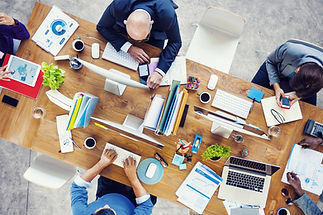 Top view of an office desk and people working around it