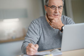 Senior man at home connected on laptop c