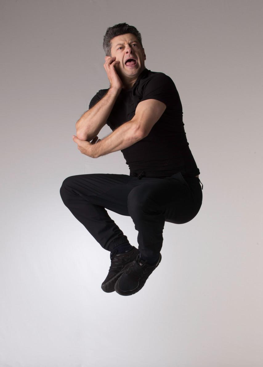 Andy Serkis jumping desk pose