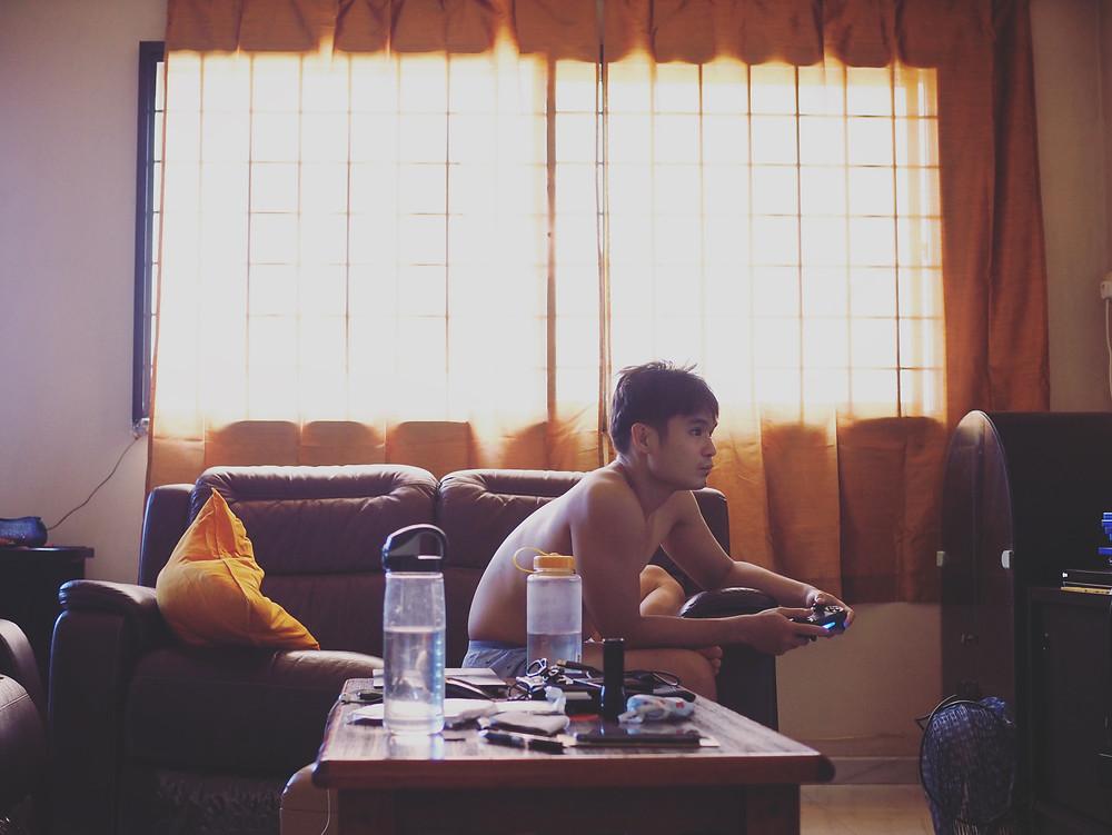 四方脸坐在沙发上玩PS4。