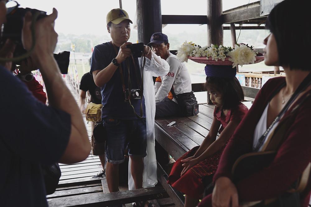 大家围着避雨的小女孩继续拍摄