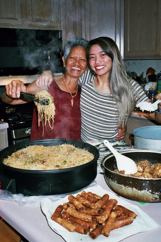 My lola and I with pancit, adobo, and lumpia, in 2018.