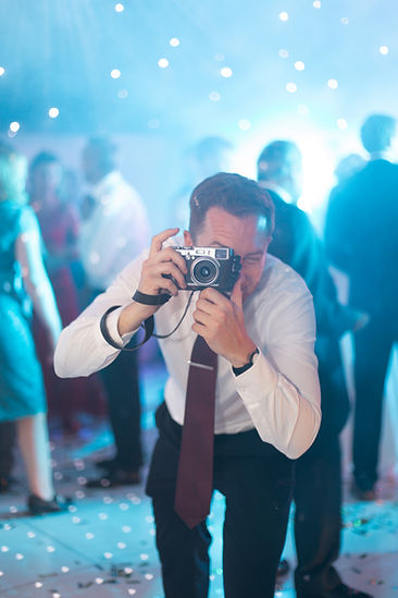 Guest taking film photo on dancefloor