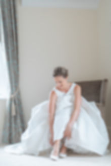 Smiling bride putting on heels in Jesus Peiro wedding dress from Miss Bush Bridal