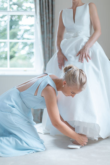 Maid of honour fastening brides shoes in wedding dress