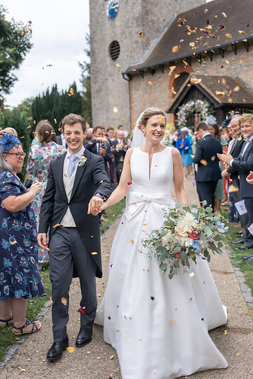 Bride and groom smiling during confetti moment wearing Jesus Peiro wedding dress from Miss Bush Bridal