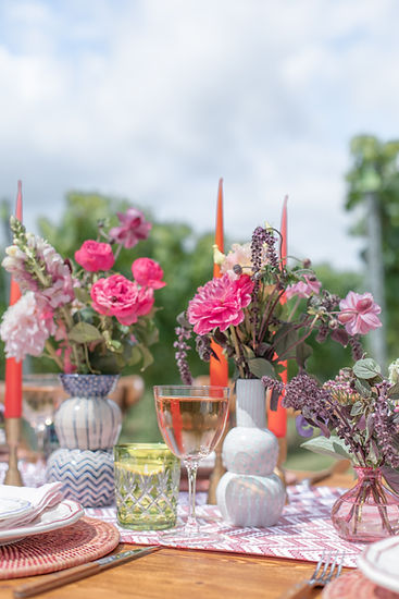 Pink flowers in vase with pink candlesticks for colourful rustic styled tablescape shoot