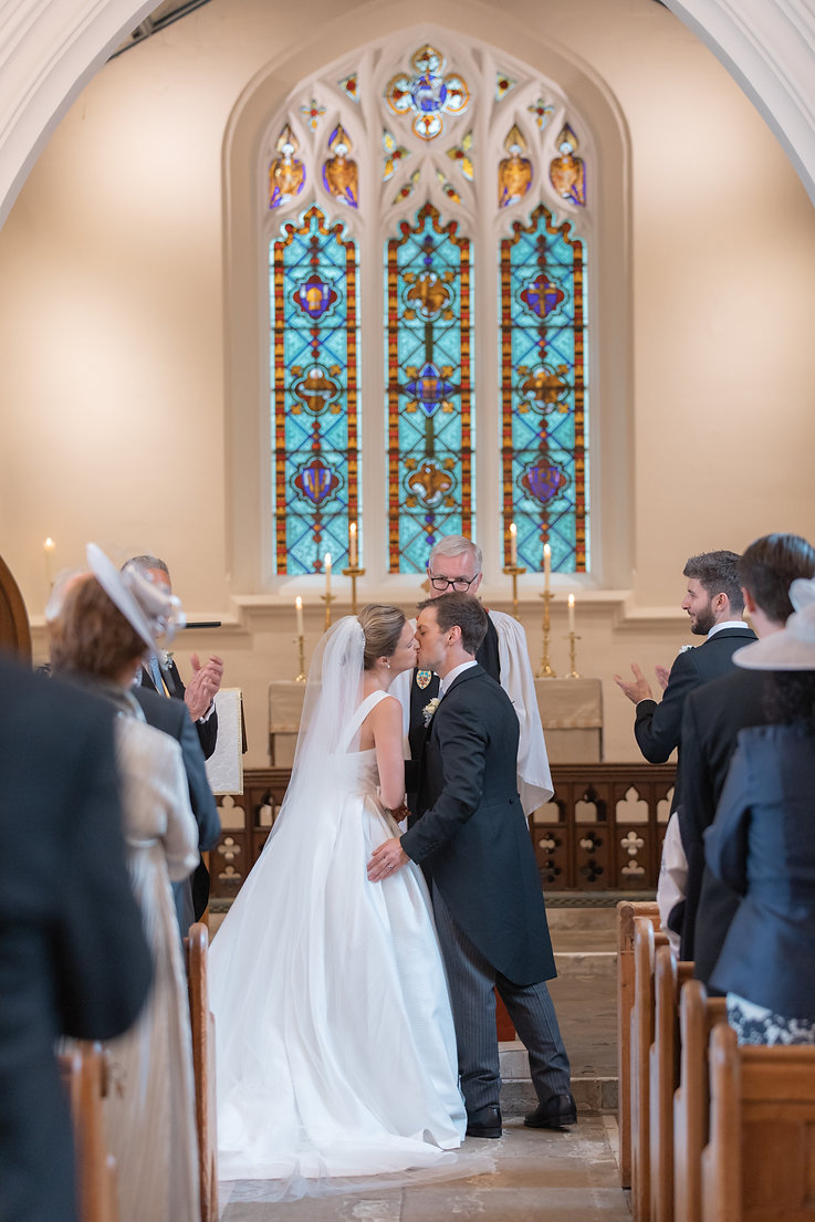 Bride and groom first kiss in church with stain glass windows
