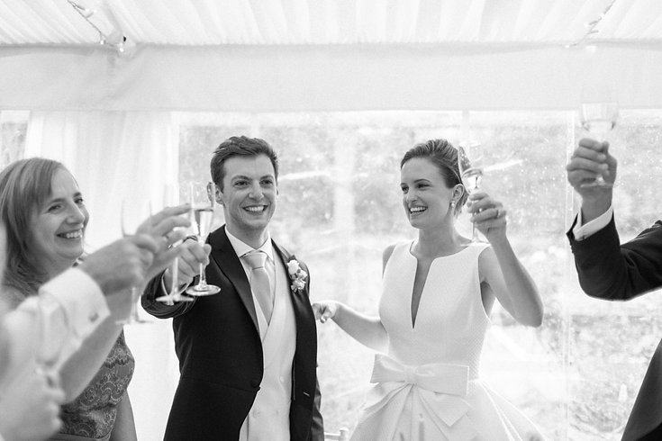Bride and groom standing raising a glass champagne cheers