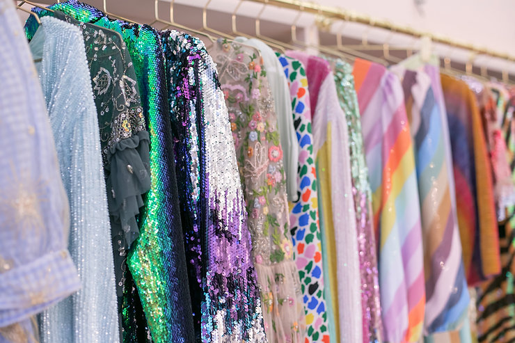 Rail of colourful sequin sparkle patterened dresses by Rixo Ganni and Olivia Rubin rented from Hurr