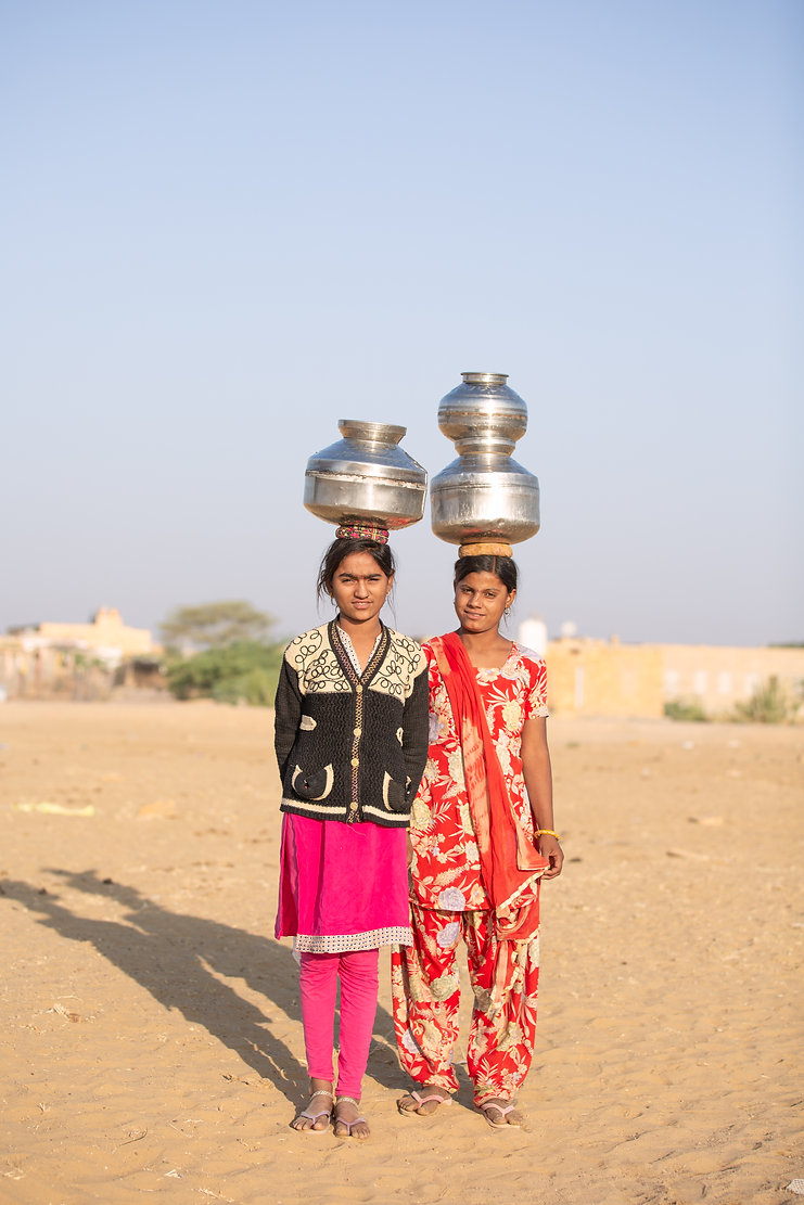 Portrait of young girls carrying water on head in Jaisalmer desert sunset golden hour
