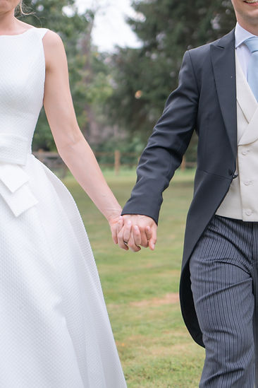 Bride and groom close up holding hands