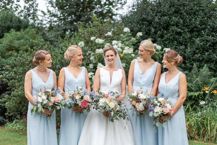 Bride with bridesmaids smiling and laughing holding flower bouquets