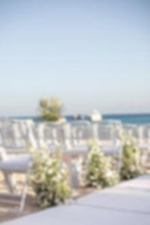 Green and white chair flowers Greek beach wedding ceremony in Mykonos