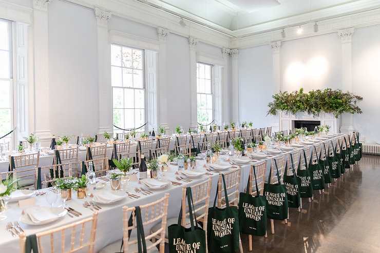 Wide shot of long tables with foliage and fireplace for The Wing London event at ICA Gallery