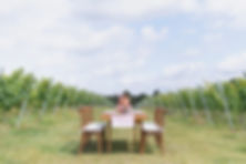 Long wooden table and chairs with pink runner and candlesticks for styled tablescapes shoot in field