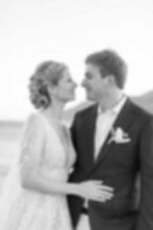 Romantic black and white bride and groom posing on beach in Greece