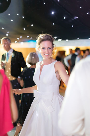 Bride smiling and dancing on dancefloor