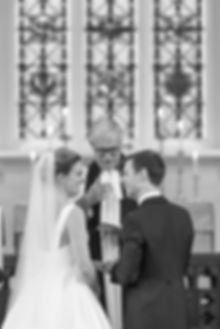 Bride and groom looking at each other laughing in church with stain glass windows