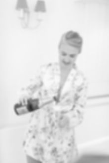 Bridesmaid popping bottle of champagne on wedding day getting ready morning