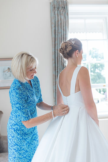 Brides mother fastening back of wedding dress in front of window