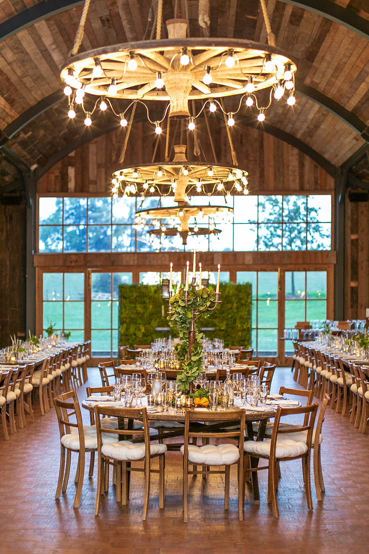 Tablescape of The Hay Barn at Soho Farmhouse with wooden chairs, chandeliers and foliage centrepiece
