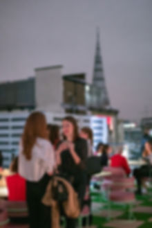 Members on rooftop balcony at night at The Wing London launch party