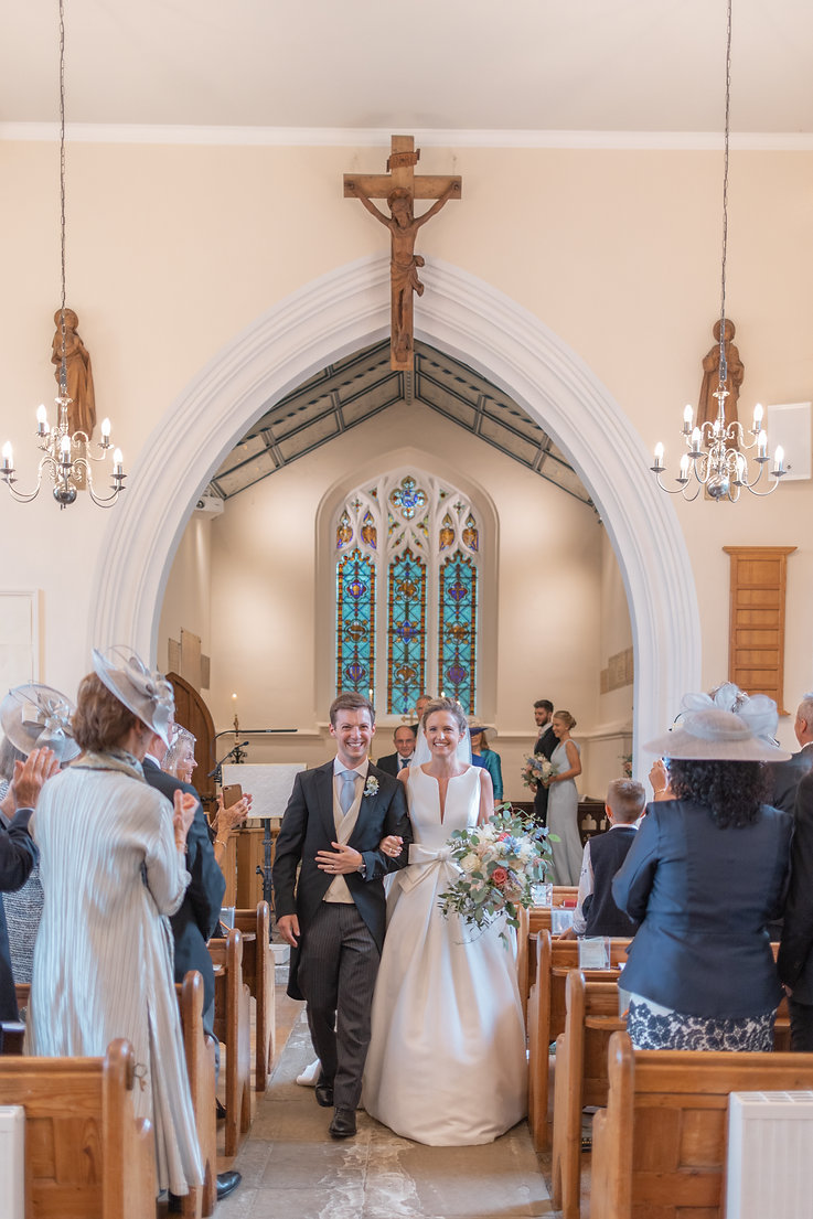 Bride and groom walking down aisle leaving church wedding ceremony