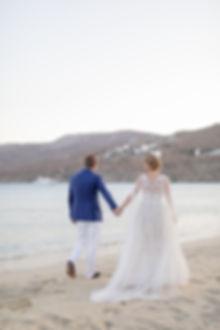 Bride and groom holding hands walking down beach in Mykonos Greece