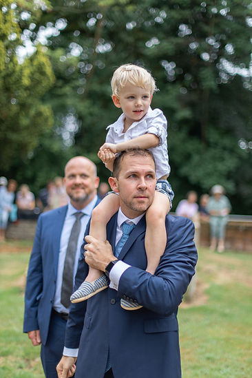 Young boy on fathers shoulders at wedding
