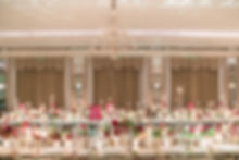 Candlelit long table tablescape with green red and pink flowers at Claridges ballroom luxury event