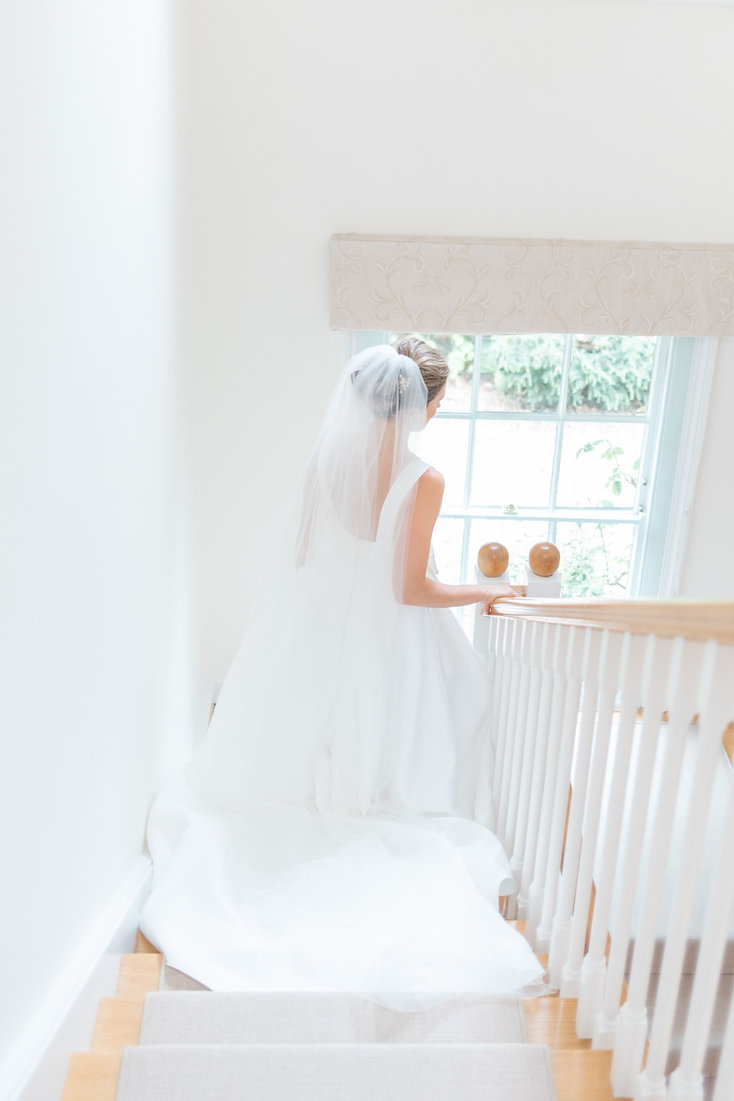 Bride walking down stairs in Jesus Peiro wedding dress from Miss Bush Bridal