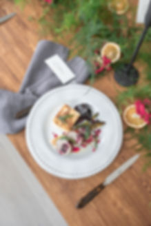 Christmas meal on wooden table with foliage runner with grey candlesticks for autumnal winter tablescape styled shoot inspiration
