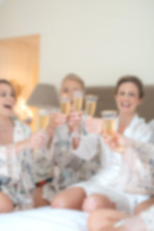Bridal party champagne glasses cheers on bed in floral dressing gowns English wedding