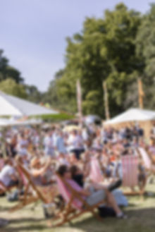 Crowds sitting on stripy deck chairs at Soho House Festival
