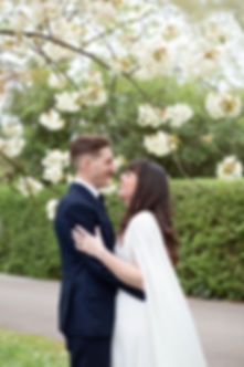 Bride and Groom smiling under blossom tree in Regent's Park luxury London wedding photographer
