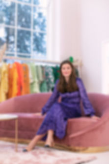 Luxury sustainable fashion rental company Hurr founder and CEO Victoria Prew sitting on pink sofa at pop up shop