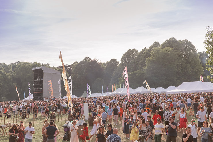 Wide shot of british festival with crowds at golden hour at Soho House Festival