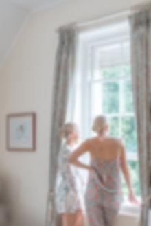 Bridesmaids in floral pajamas looking out of window English wedding